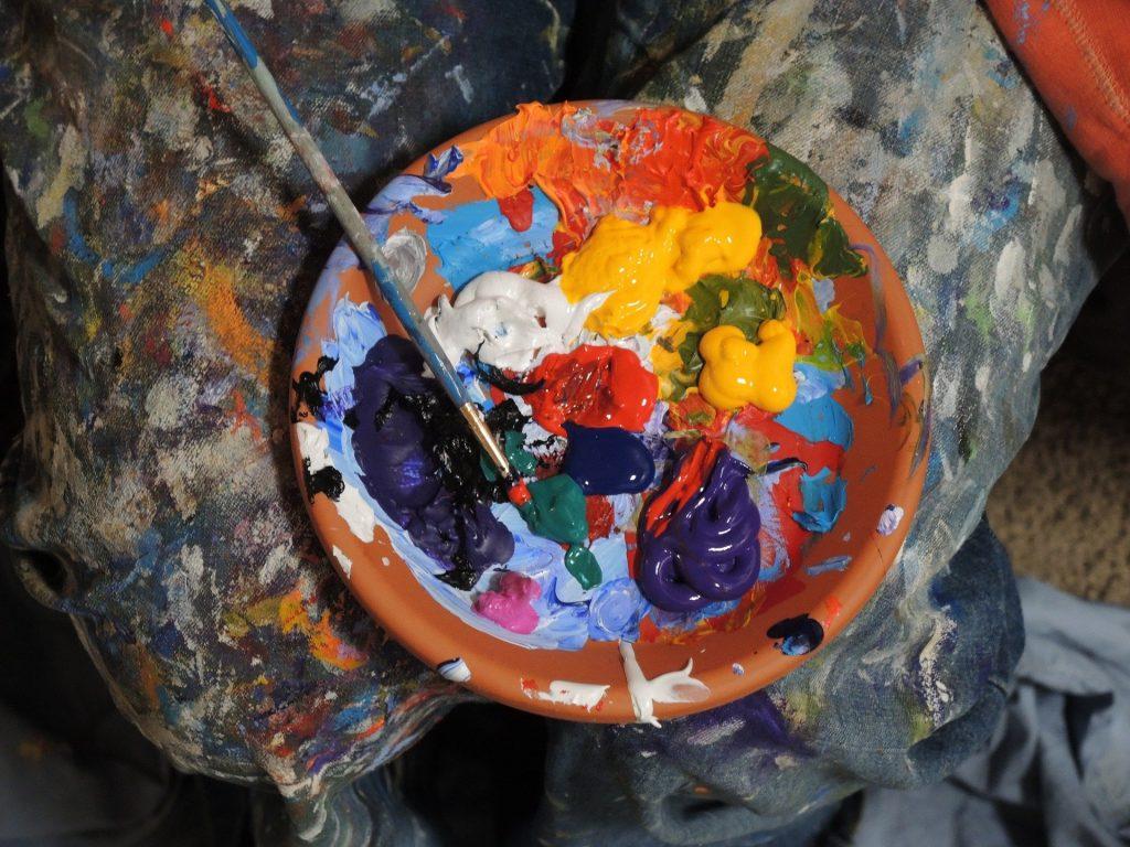 plusieurs couleurs de peinture dans un bol en terre posé sur les jambes de l'artiste