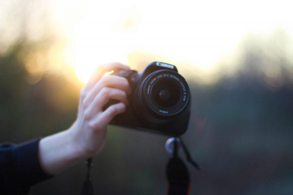 main qui tient un appareil photo